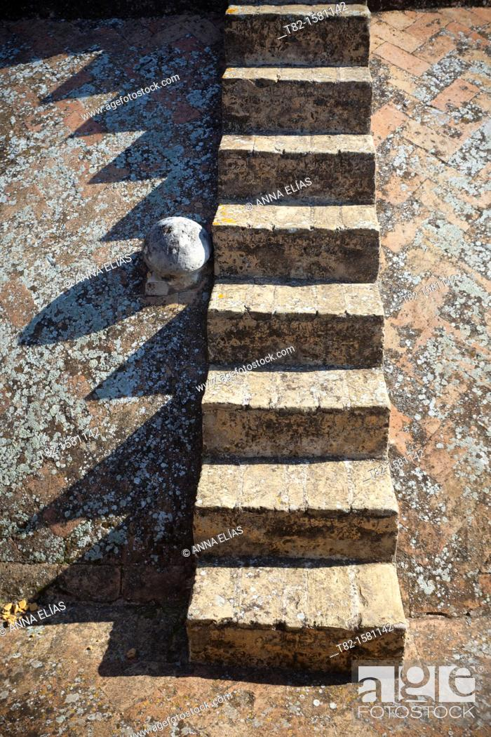 Stock Photo: vertical stone staircase with texture and shadows.