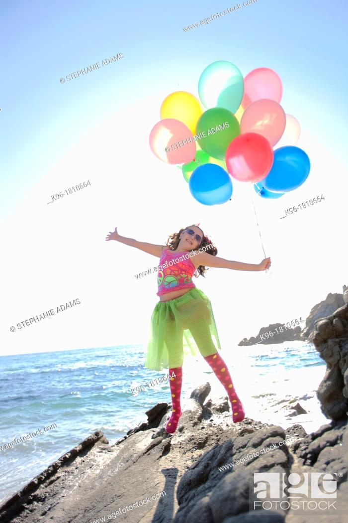 Stock Photo: little girl jumping with joy holding balloons while at the ocean.