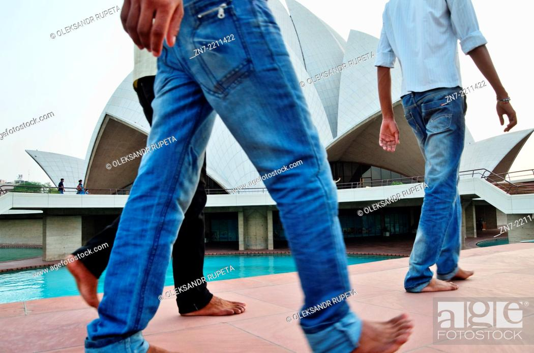 Stock Photo: Indian visitors walking barefoot in front of Lotus Temple, India.