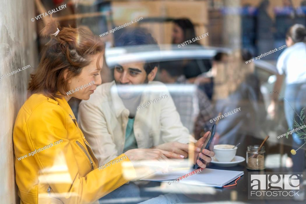 Stock Photo: Man and woman with cell phone and notebook meeting in a cafe.