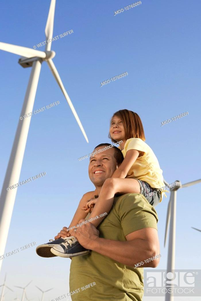 Stock Photo: Father and daughter 5-6 on wind farm side view.