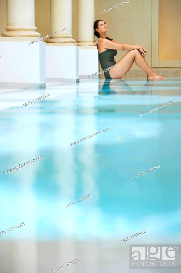 Stock Photo: Young woman sitting by swimming pool portrait side view.
