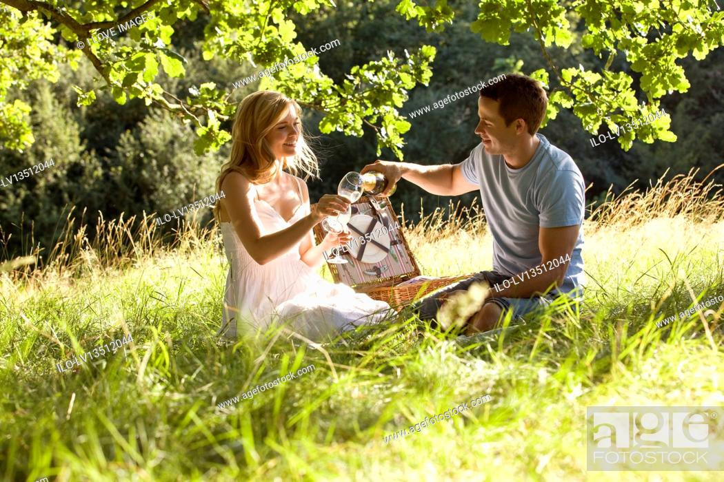Stock Photo: A young couple having a picnic, man pouring sparkling wine.