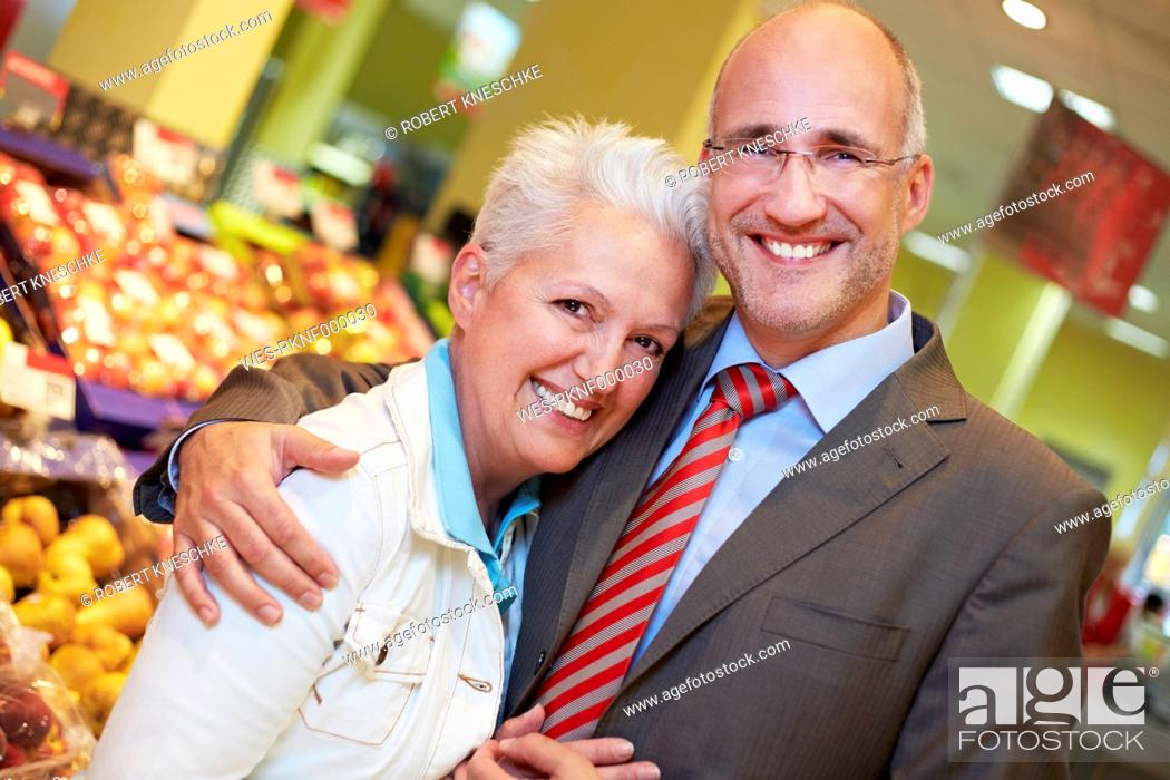 Stock Photo: Germany, Cologne, Mature couple in supermarket, smiling, portrait.