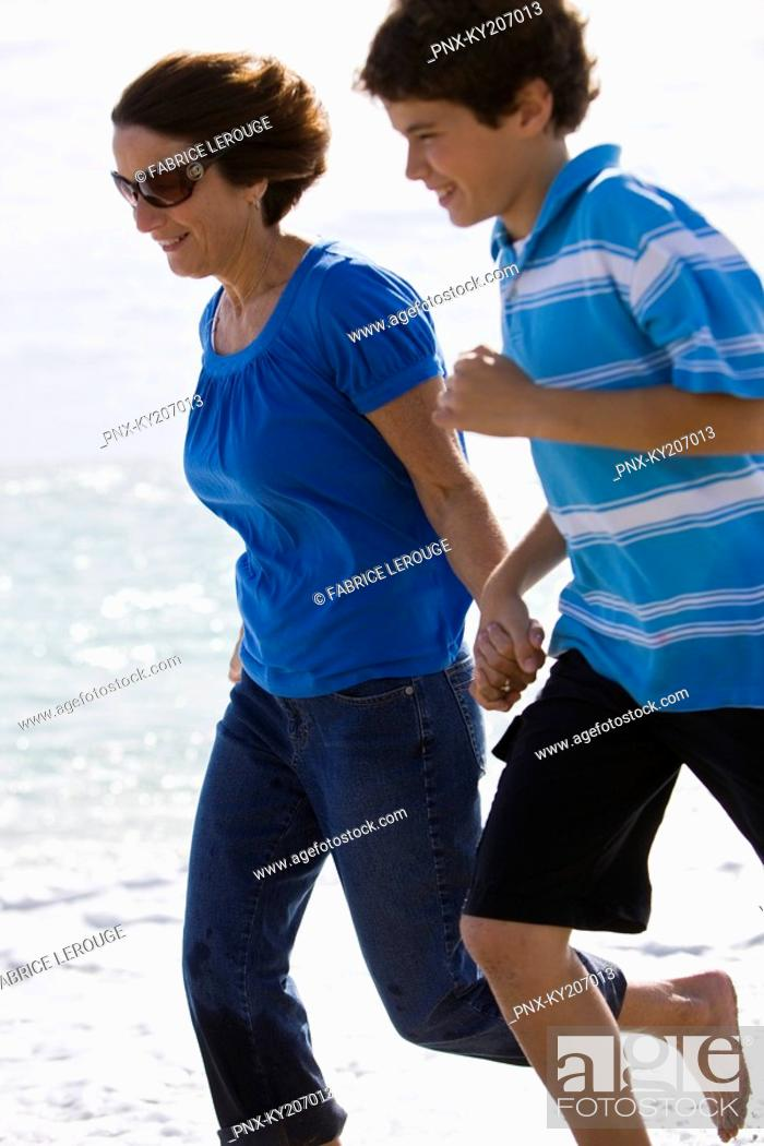 Stock Photo: Woman running on the beach with her grandson.