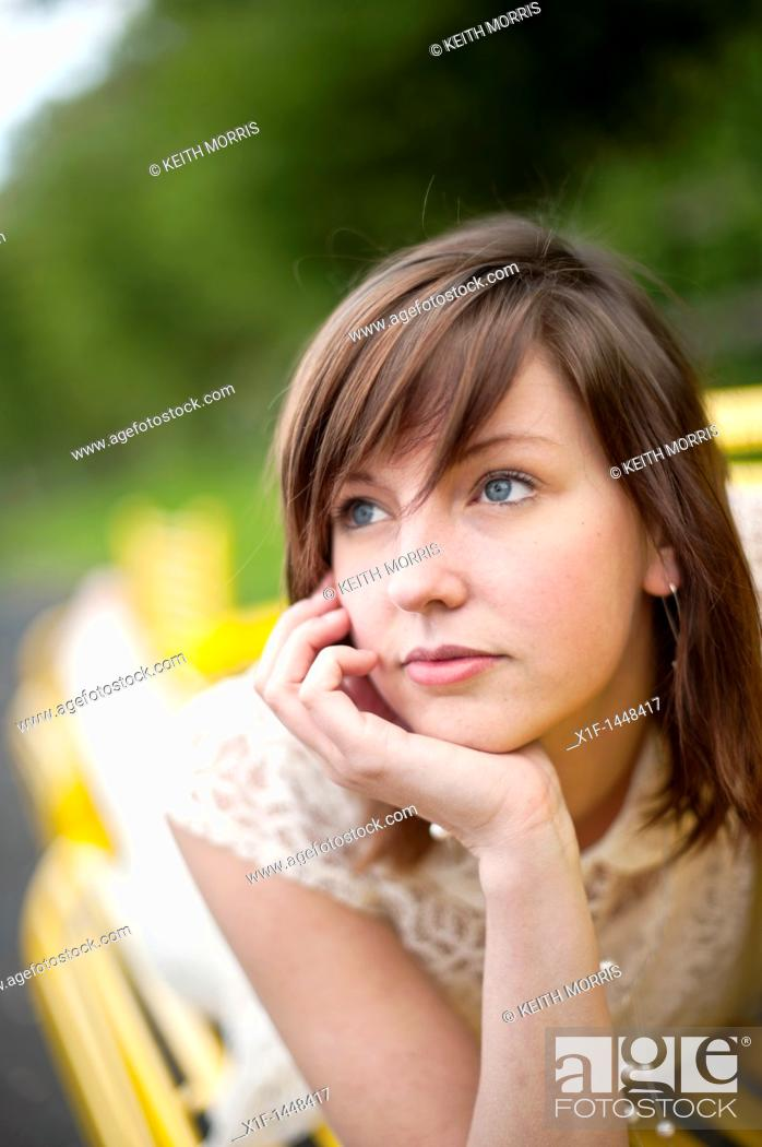 Stock Photo: A young slim attractive girl in her late teens or early 20's thinking, looking pensive thoughtful, UK.