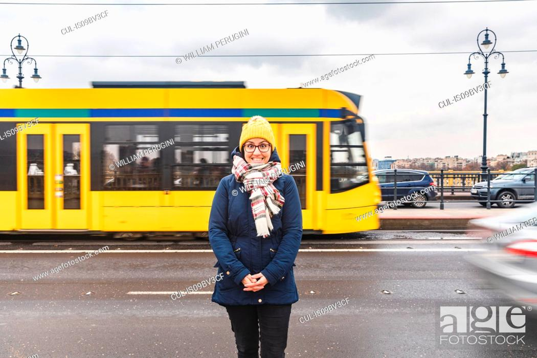 Stock Photo: Woman posing on roadside, tram passing by in background, Budapest, Hungary.