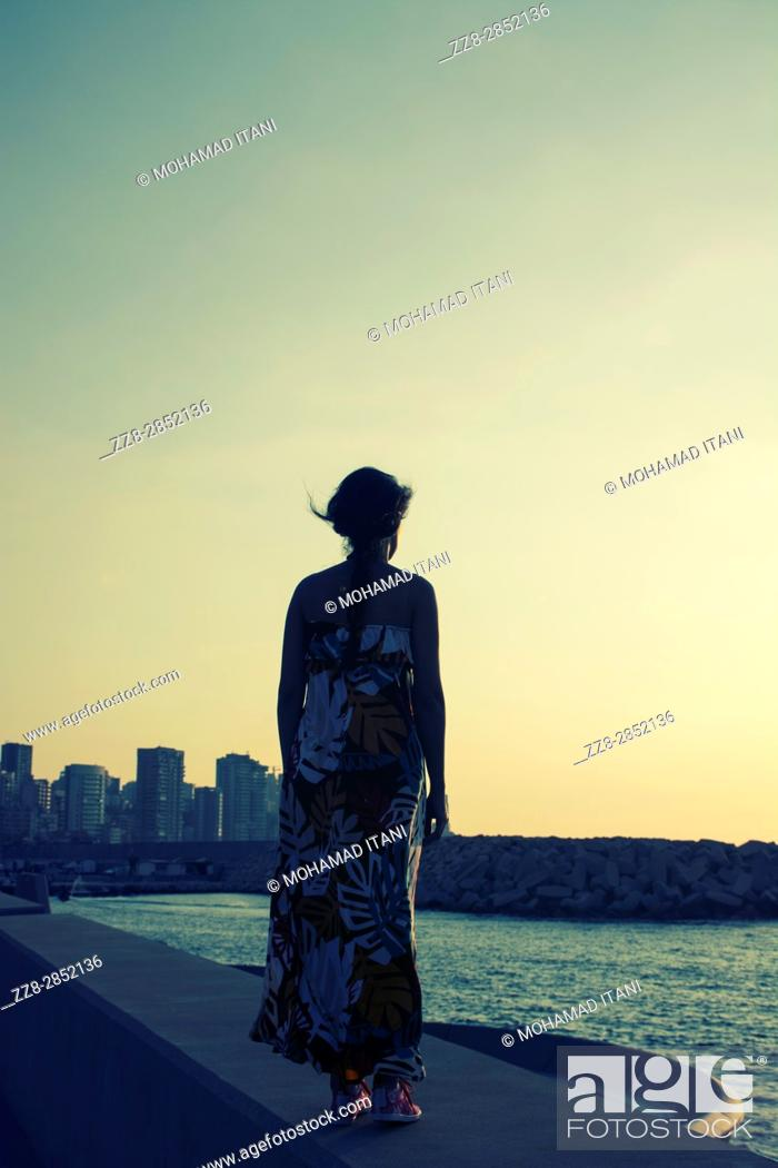 Stock Photo: Rear view of a woman wearing a summer dress standing against the skyline.