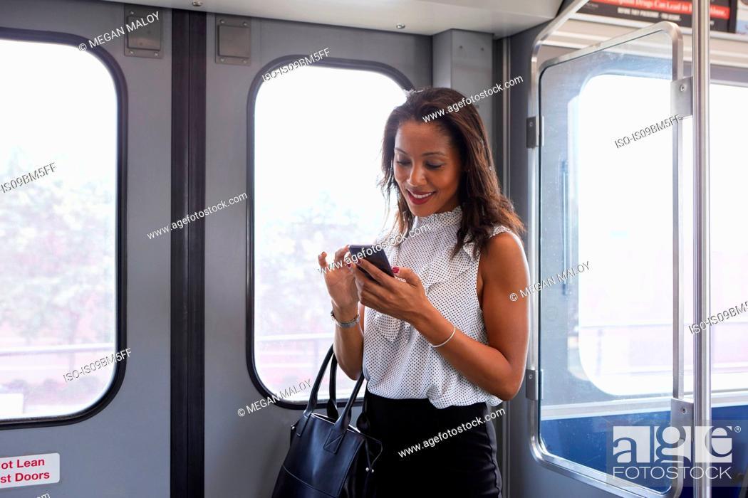 Stock Photo: Businesswoman using cellphone in train.