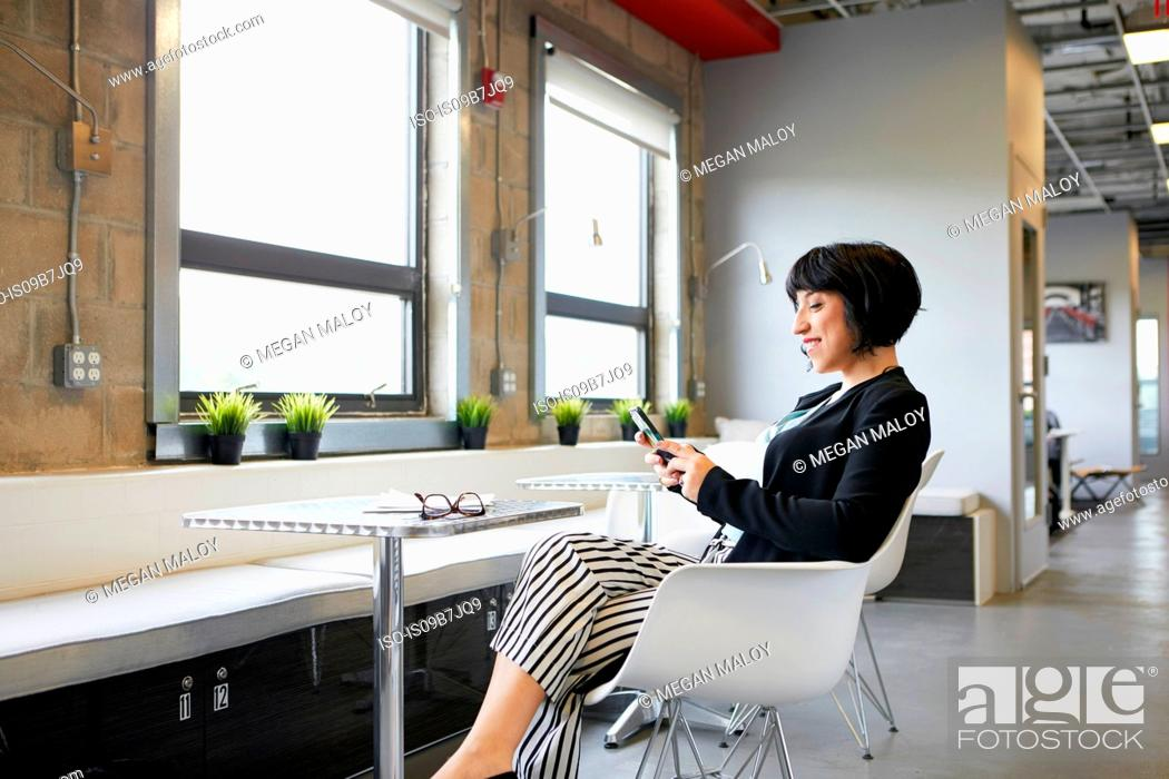 Stock Photo: Businesswoman sitting at table in office environment, looking at smartphone.