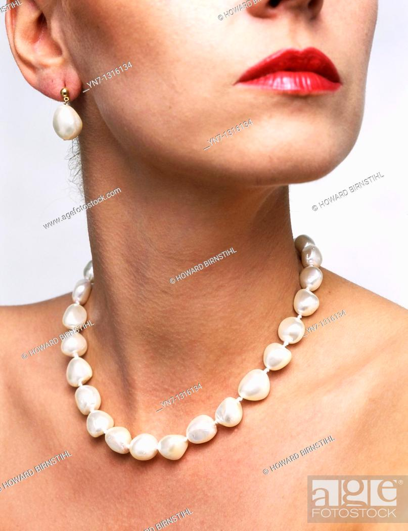 Stock Photo: close up view of models neck with string of pearls with earrings.