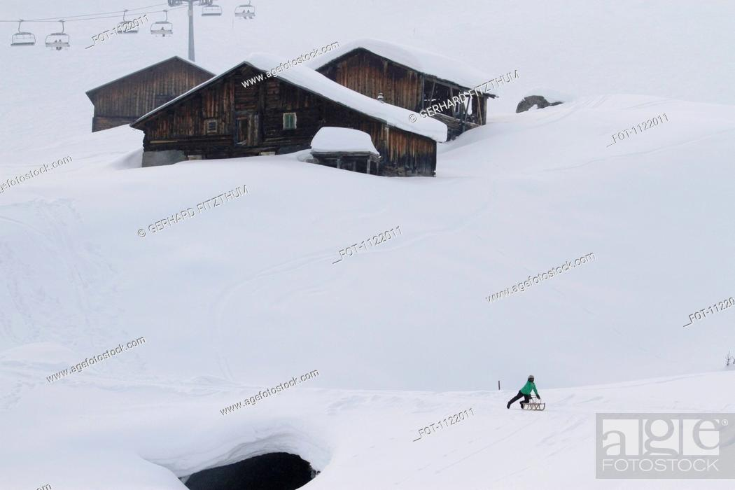 Stock Photo: Child on sledge below log cabins on snowy hill.