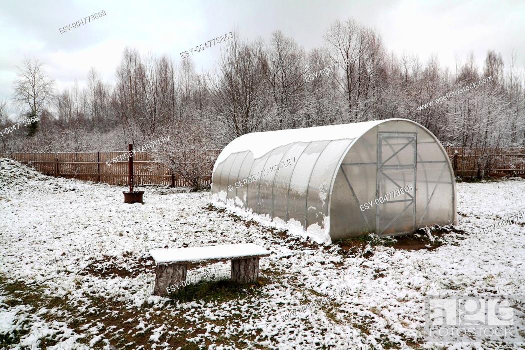 Stock Photo: plastic hothouse in winter garden.