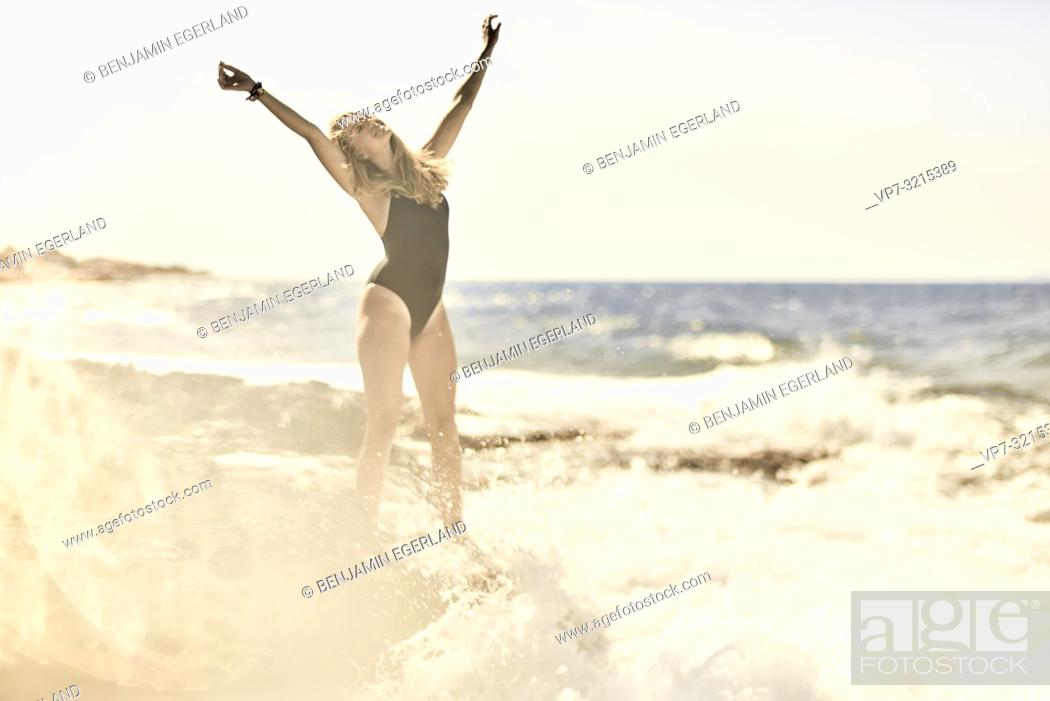 Photo de stock: young woman stretching arms at seaside enjoying summer holiday and freedom, in Crete, Greece.