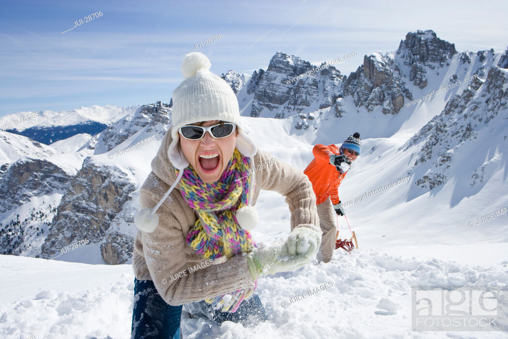 Stock Photo: Smiling couple with sled climbing hill with mountain in background.