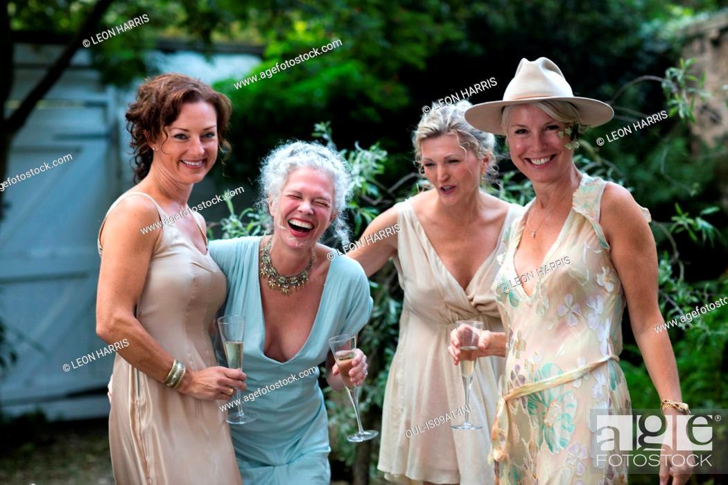 Stock Photo - Elegant mature women enjoying champagne in urban garden