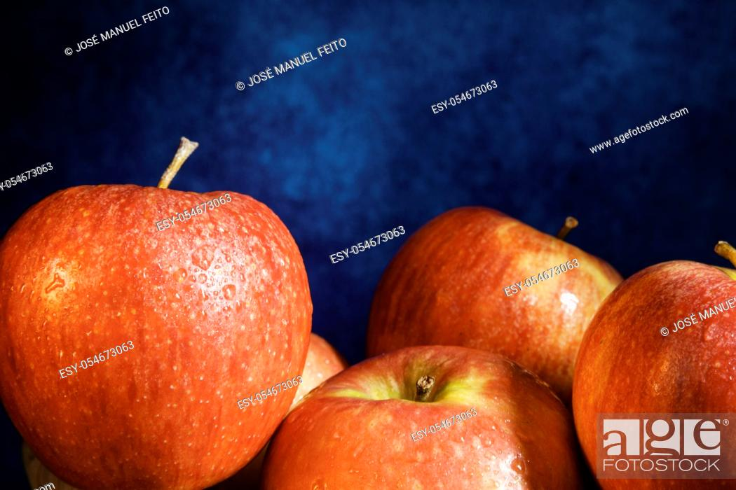 Stock Photo: Delicious red apples group close-up on abstract blue background.