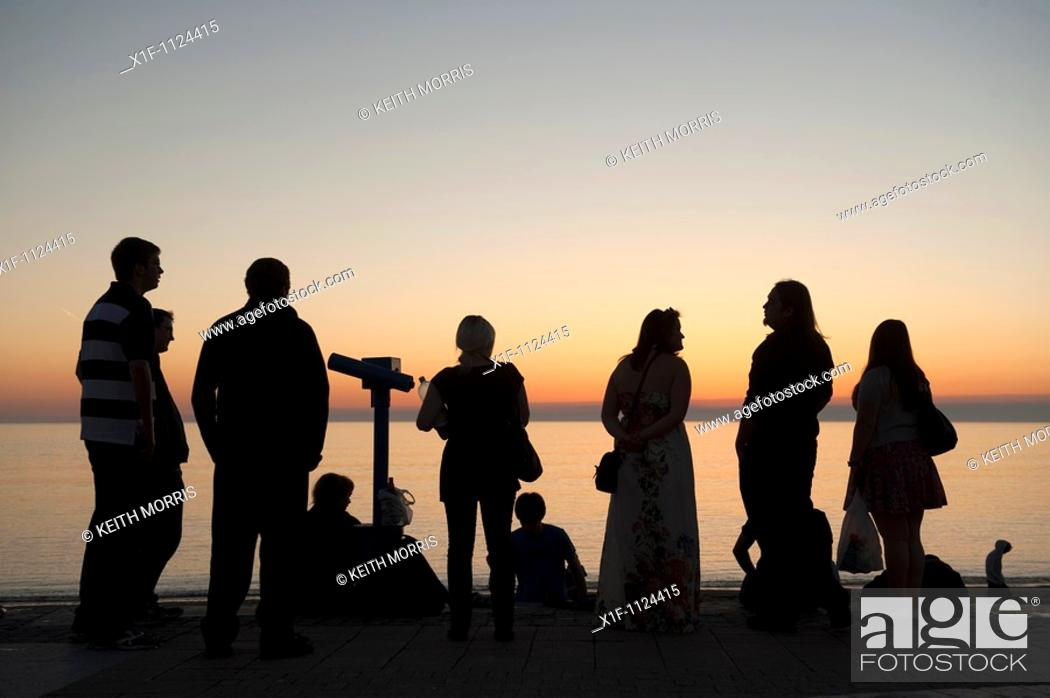 Stock Photo: A group of people in silhouette looking at the sunset over Cartdigan Bay, Ceredigion westWales UK.
