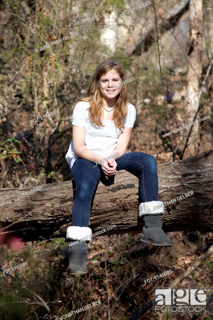 Stock Photo: Girl sitting on tree trunk in Mooresville, North Carolina, USA.