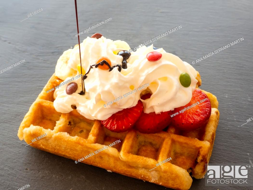 Imagen: Chocolate syrup falling on a Belgian waffle with cream and colorful chocolates on pieces of strawberry on a slate plate.