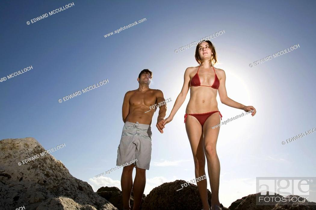 Stock Photo: Couple walking across rocks and holding hands.