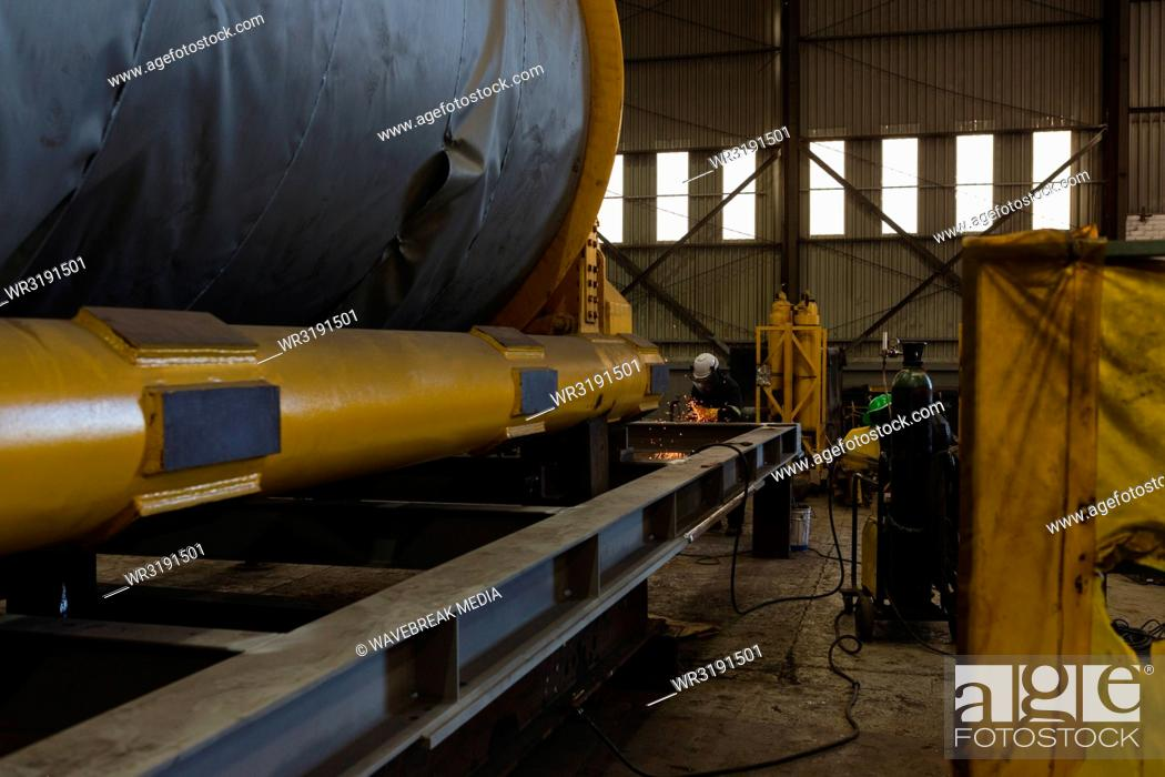 Stock Photo: Welder repairing vessel part.