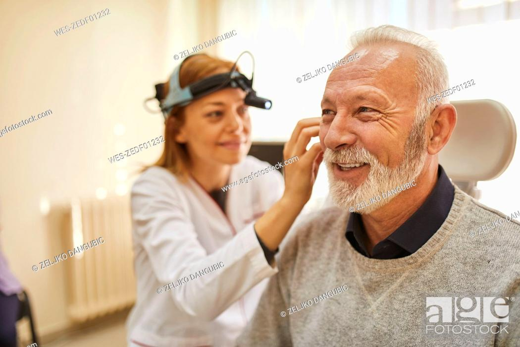 Stock Photo: ENT physician examining ear of a senior man.