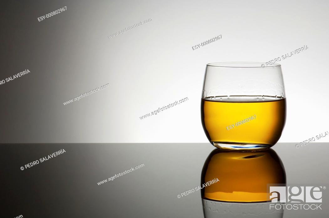 Stock Photo: closeup of a glass of whiskey with a white background.