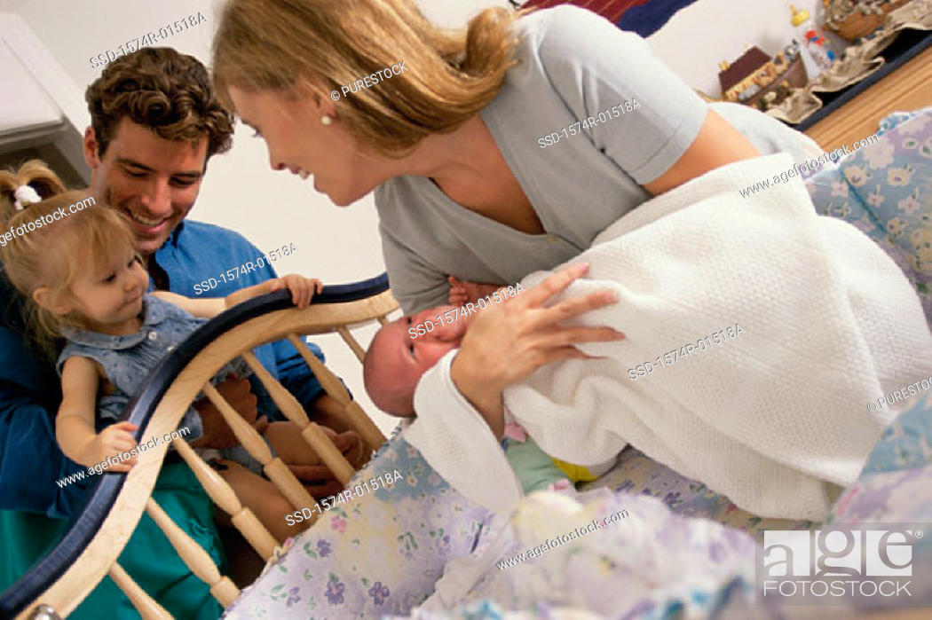 Stock Photo: Mother placing her baby into a crib.