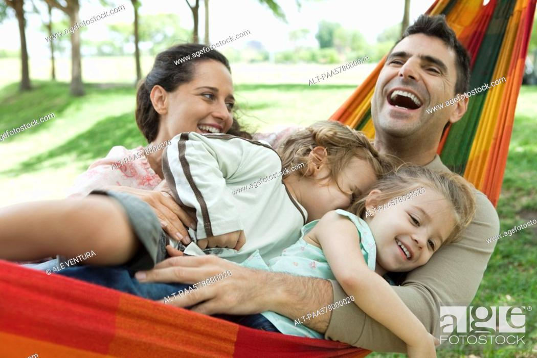 Stock Photo: Family laughing together on hammock.