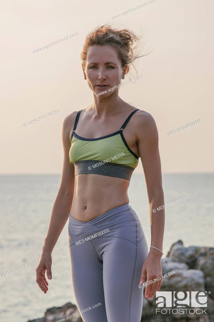 Imagen: Woman in fitness clothing standing by the sea.