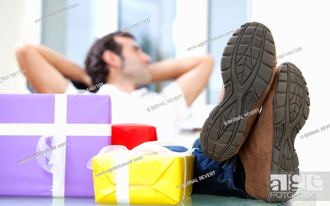 Stock Photo: A man rests happily next to a pile of presents.