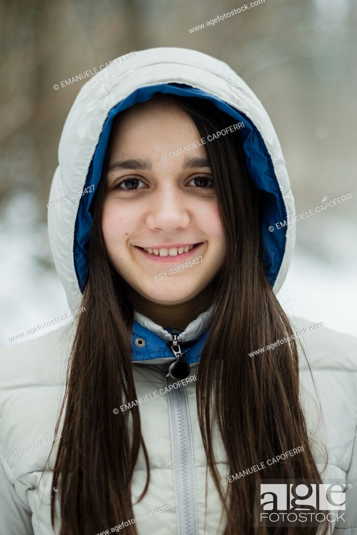 Stock Photo: portrait of an 11-year-old girl outside under a snowfall, in a forest, dressed in a down jacket, a windbreaker.