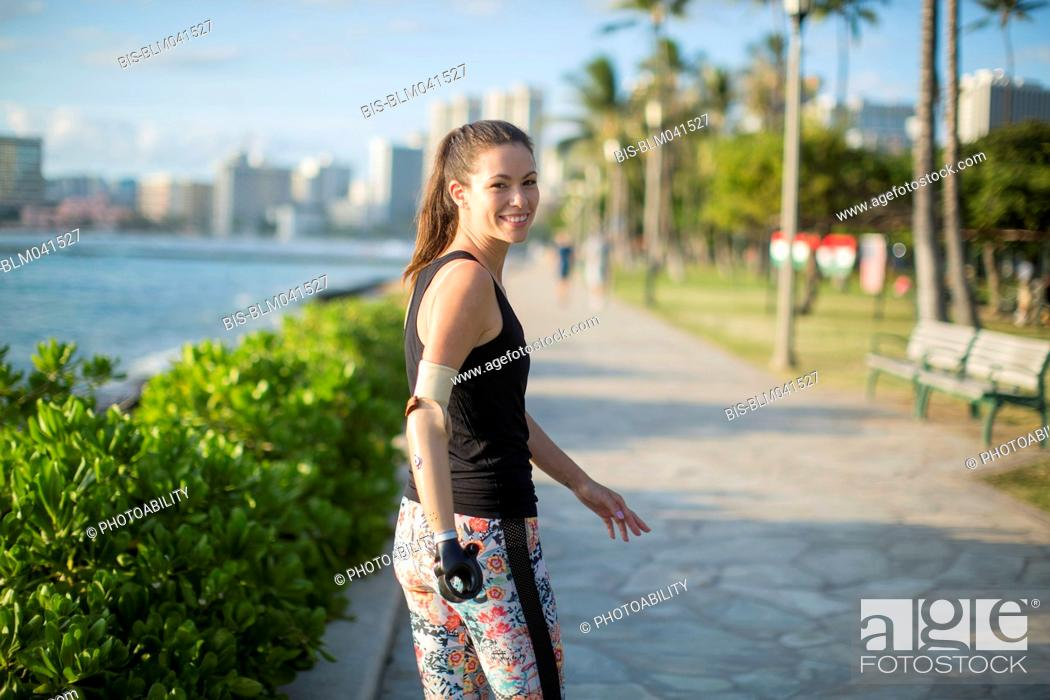 Imagen: Mixed race amputee athlete walking on urban waterfront.