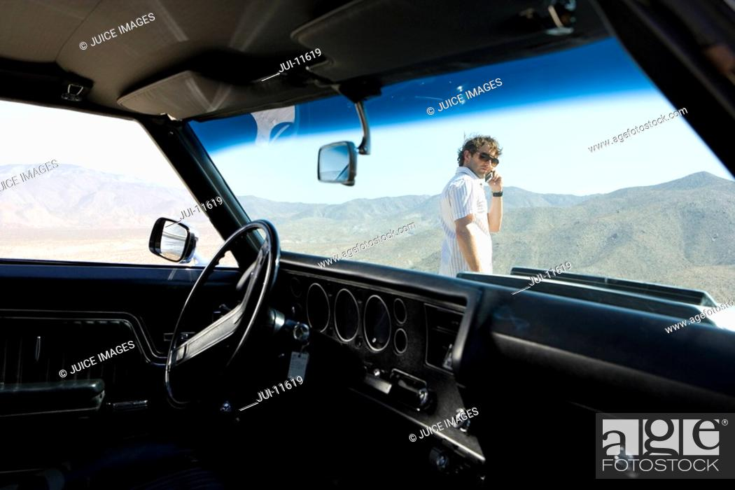 Photo de stock: Young man in sunglasses using mobile phone by car in desert, view through windscreen of car.