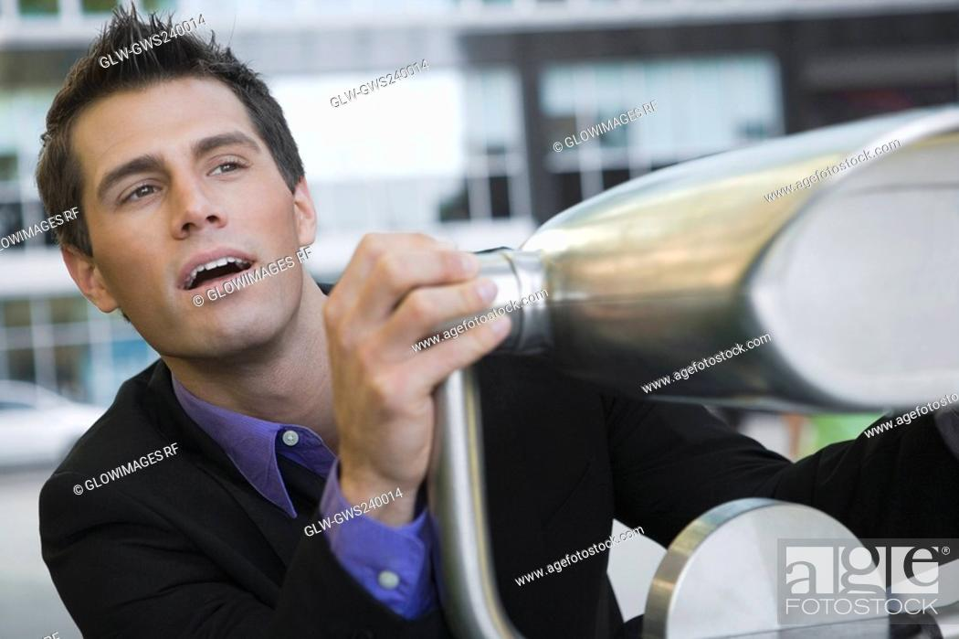 Stock Photo: Close-up of a businessman holding a coin-operated binoculars.