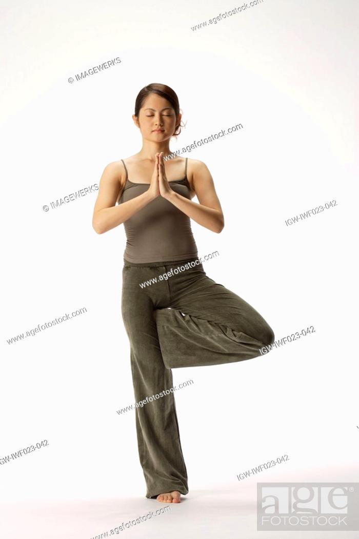 Stock Photo: View of a young woman in tree position.