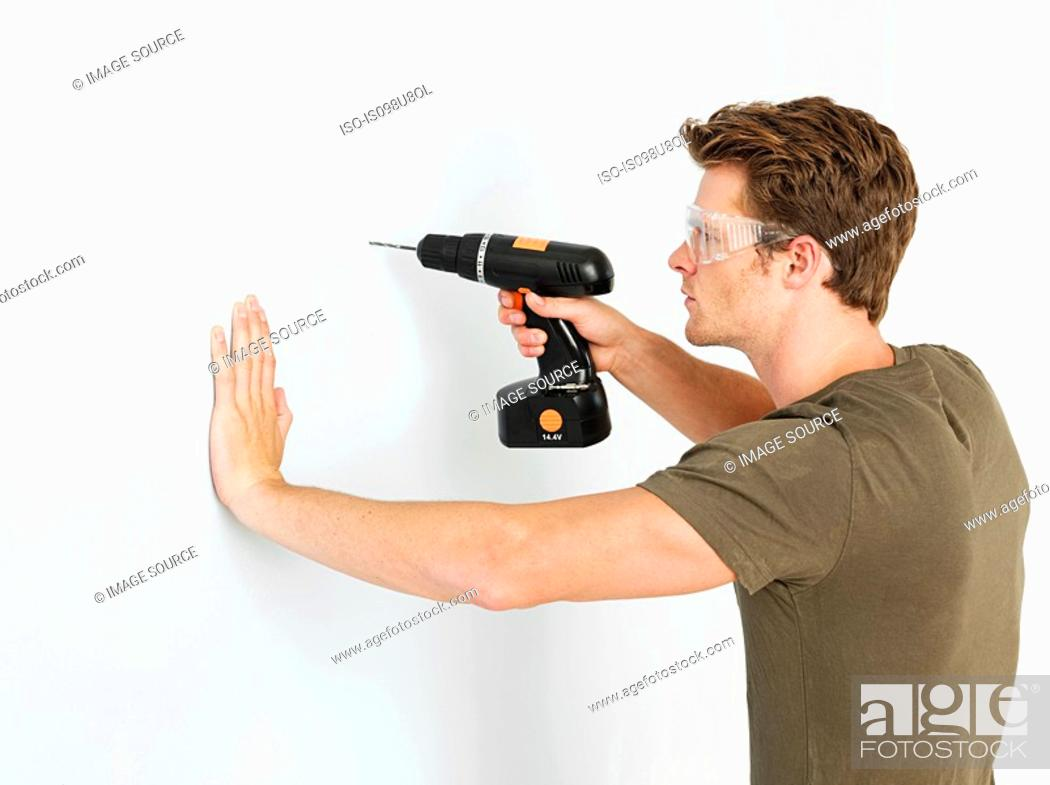 Stock Photo: Young man using electric drill.