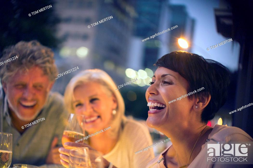 Stock Photo: Laughing friends drinking white wine at urban sidewalk cafe.