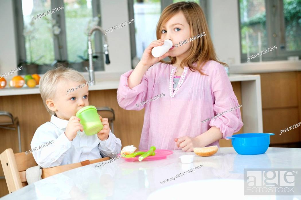 Stock Photo: Girl drinking milk with her brother drinking juice at a breakfast table.