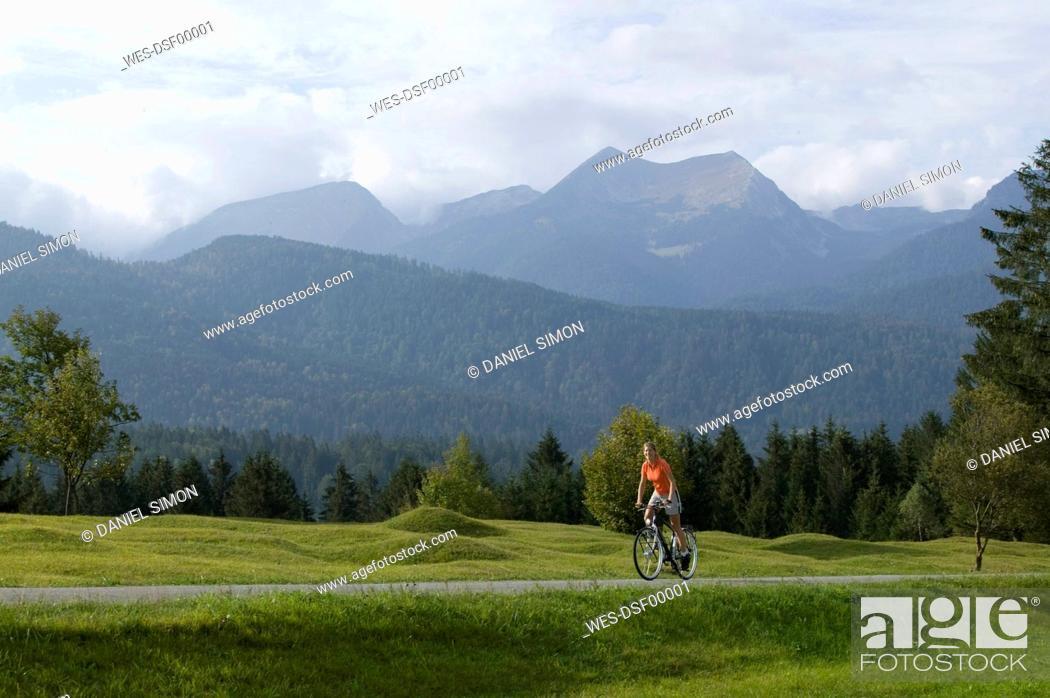 Stock Photo: Germany, Bavaria, Mittenwald, Woman mountain biking against mountain scenery.