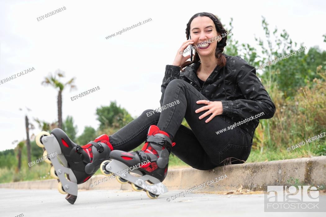 Stock Photo: Happy Woman on roller skating pause, sitting on the street and using mobile phone. Pretty, Urban Girl talking on the Phone, wearing Roller Skates.