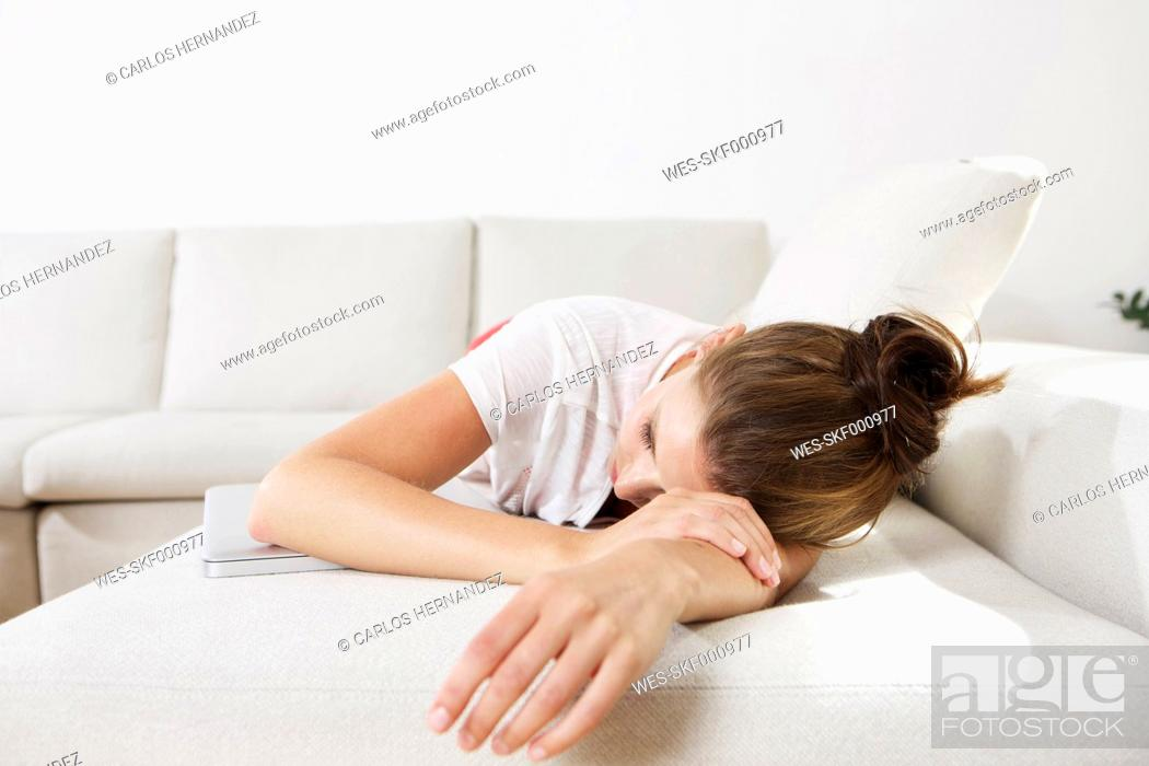 Stock Photo: Germany, Berlin, Young woman lying on couch.