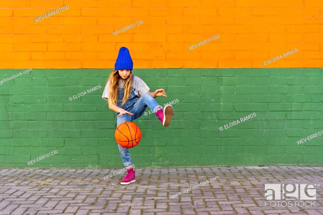 Stock Photo: Young girl playing basketball, dribbling and lifting leg.