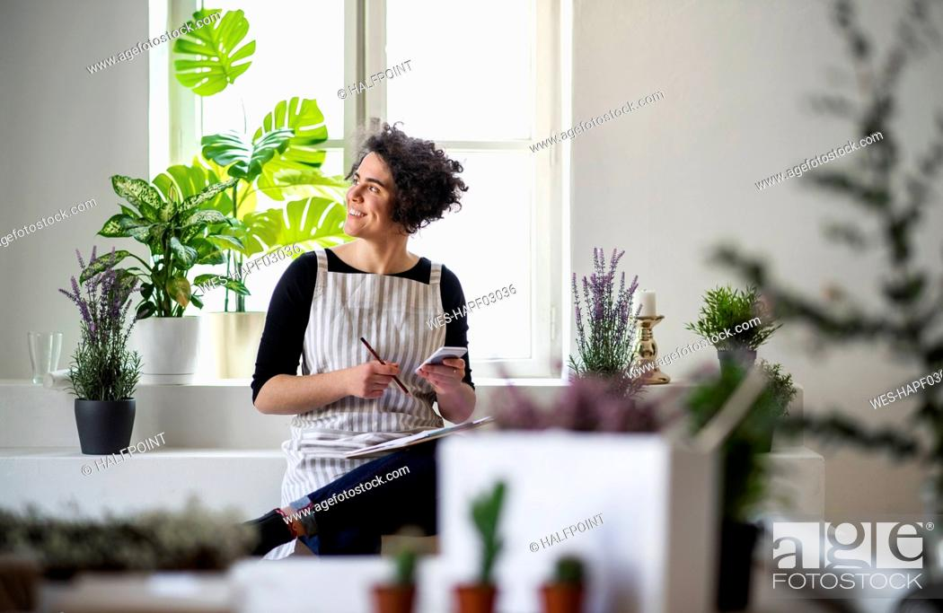 Stock Photo: Smiling young woman with clipboard and cell phone in a small shop with plants.