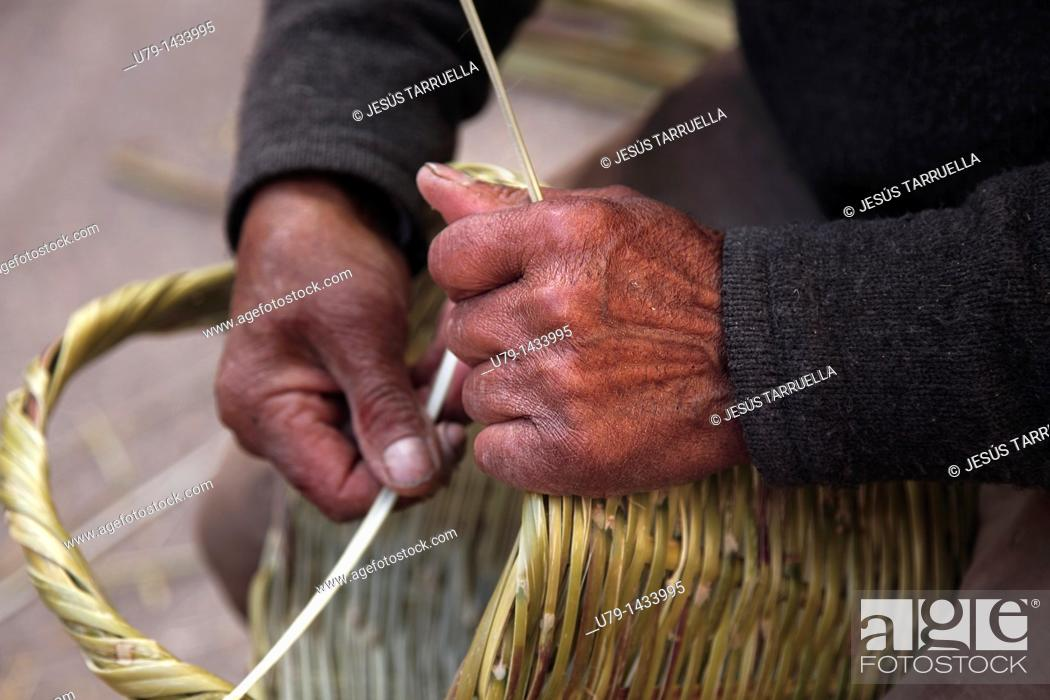 Stock Photo: Detail of the hands of a craftsman working on a basket in Villena Medieval Fair on March 15, 2011.
