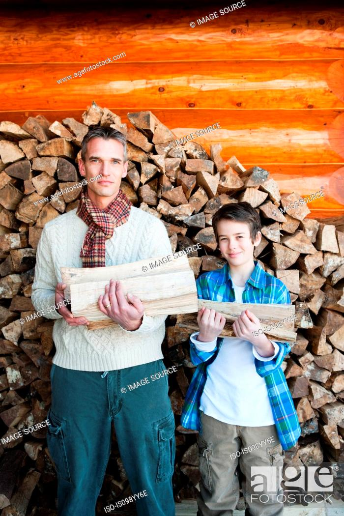 Stock Photo: Father and son holding logs, portrait.