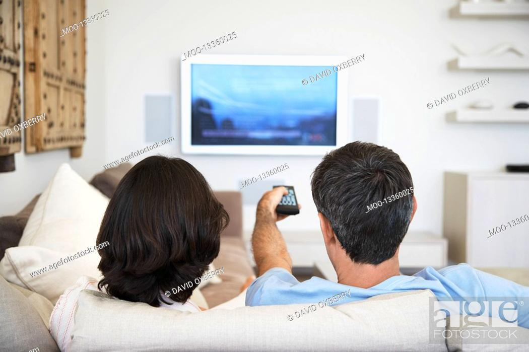 Stock Photo: Couple using remote control sitting in front of television in living room back view.