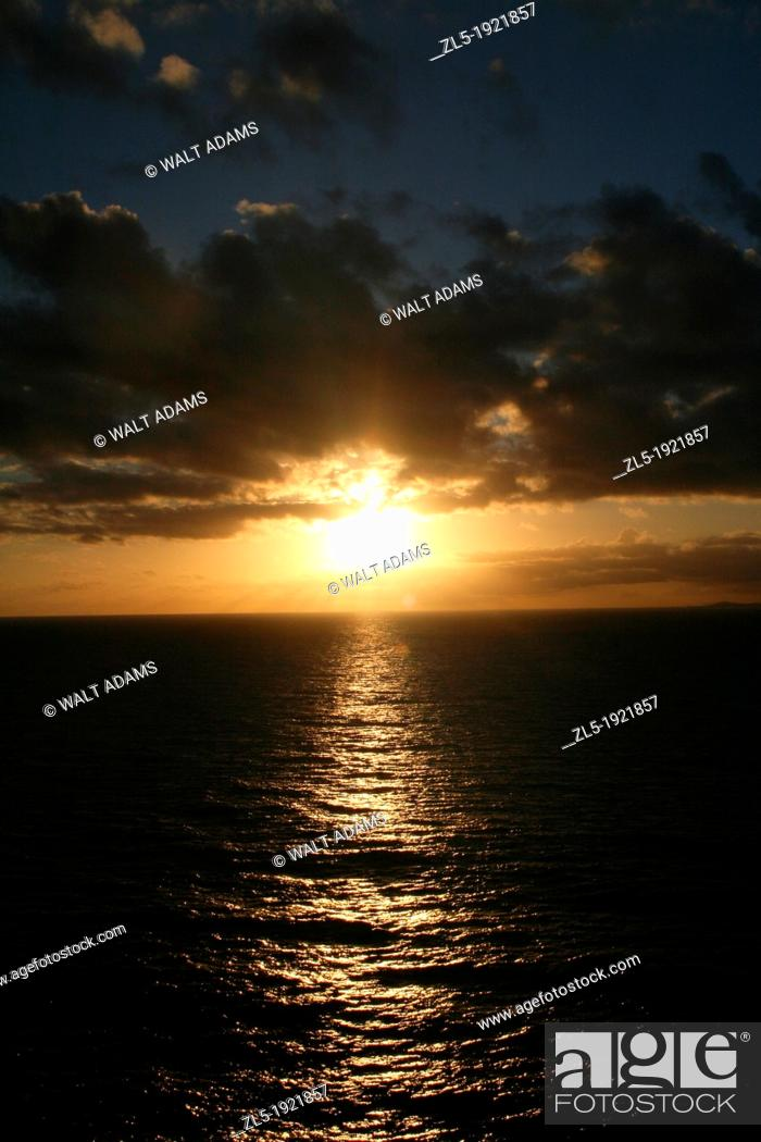 Stock Photo: The sailors watch in awe as the sun peeks below a bank of clouds as it begins to disappear below the horizon.