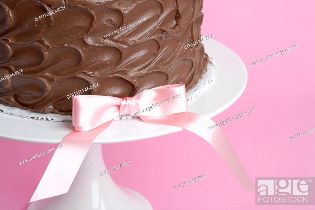 Stock Photo: Pink ribbon bow on chocolate cake (close-up).